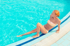 Young woman sunbathing by the pool Stock Image