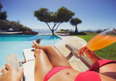 Young woman sunbathing by the poolside drinking fruit juice Royalty Free Stock Photography