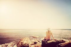 Young woman sunbathing on rocky beach. Vintage Royalty Free Stock Image