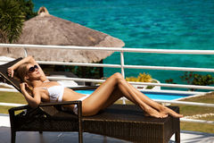 Young woman sunbathing on sunbed. Young woman lie on sunbed and sunbathing. Luxury sea view Royalty Free Stock Images
