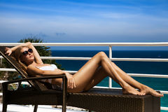 Young woman sunbathing on sunbed. Young woman lie on sunbed and sunbathing. Luxury sea view Royalty Free Stock Photography
