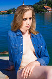 Young Woman Sunbathing on Tranquil Lake Dock. Close Up Portrait of Serious Young Blond Woman Wearing Unbuttoned Denim Shirt Sunbathing on Dock Overlooking royalty free stock images