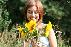 Young woman with sunflowers. A young woman smiles radiantly as she loks at some sunflowers in a field royalty free stock images