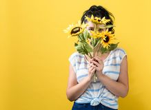Young woman with sunflowers. On a yellow background royalty free stock photo