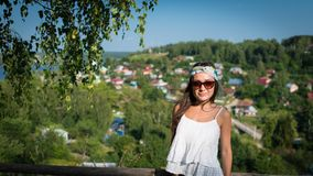 Young woman in sunglass and white dress stands on a hill. In warm summer day and looking in camera. Stylish girl is standing in the park on the background of a Royalty Free Stock Images