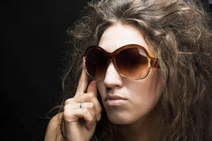 Young woman in sunglasses. Portrait of young woman in sunglasses on the dark background Stock Photo