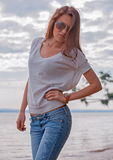 Young woman in sunglasses. Trendy young woman in sunglasses walking with sea in background Stock Photos