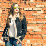 Young woman in sunglasses  against red brick wall. Royalty Free Stock Images