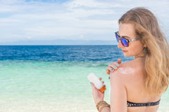 Young woman with sunglasses applyng sun protector cream at her hand on the beach close to tropical turquoise sea under Stock Photography
