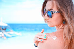 Young woman with sunglasses applyng sun protector cream at her hand on the beach close to tropical turquoise sea under blue sky. Young woman applyng sun Stock Photos