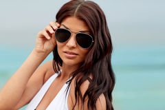 Young woman with sunglasses on beach. Summer vacation, tourism, travel, holidays and people concept -face of young woman with sunglasses on beach Royalty Free Stock Photos