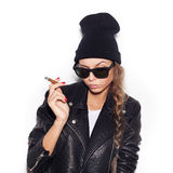 Young woman in sunglasses and black leather jacket smoking cigar Stock Photos