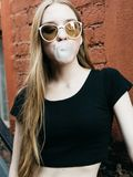 Young woman in sunglasses blowing bubble gum stock photography