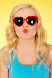 Young woman in sunglasses blowing lips kiss stock images