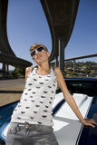Young woman in sunglasses on bonnet of car beneath overpass, low angle view Stock Photo