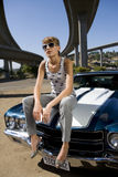 Young woman in sunglasses on bonnet of car beneath overpass, low angle view Royalty Free Stock Photos
