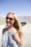 Young woman in sunglasses by car in desert, smiling, close-up Stock Photos