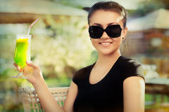 Young Woman with Sunglasses and Colorful Cocktail Drink Outside Stock Photography