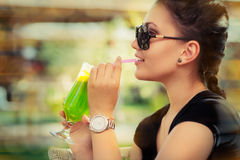 Young Woman with Sunglasses and Colorful Cocktail Drink Outside Royalty Free Stock Images