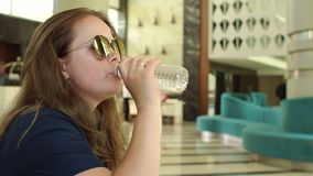 A young woman in sunglasses drinks water from a bottle in the hotel lobby. A young woman with long dark hair in sunglasses drinks water from a bottle in the stock footage