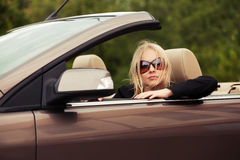 Young woman in sunglasses driving convertible car Stock Image