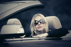 Young woman in sunglasses driving convertible car Stock Images