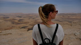 Young woman in sunglasses enjoying the stone desert view on cliff`s edge stock video
