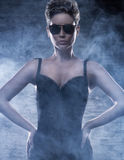 A young woman in sunglasses and erotic clothes. A young and attractive Caucasian woman posing in sunglasses and dark erotic clothes. The image is taken on a Stock Photos