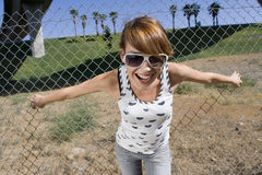 Young woman in sunglasses with hands on fence, smiling, close-up Stock Photo