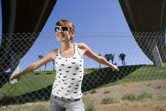Young woman in sunglasses with hands on fence, smiling, low angle view Stock Photography