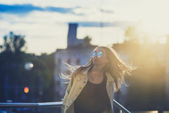 Young woman in sunglasses have fun with outdoor, sunset in the background. Young woman have fun with an outdoor swing, sunset in the background. With custom royalty free stock images