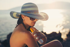 Young woman in sunglasses holding bottle of sunscreen lotion. Spraying sunblock cream on shoulder before tanning Royalty Free Stock Images
