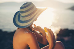 Young woman in sunglasses holding bottle of sunscreen lotion Stock Photography
