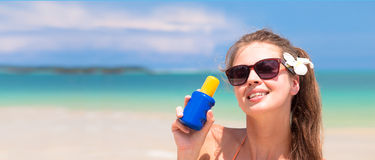 Young woman in sunglasses holding sun cream in Royalty Free Stock Photography