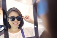 Young woman in sunglasses looking at camera in shop. Stock Photos