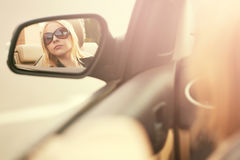 Young woman in sunglasses looking in the car rear view mirror Stock Images