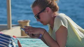 Young woman in sunglasses lying with smartphone on a beach stock video footage