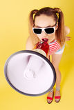 Young woman in sunglasses. With a megaphone in his hand on a yellow background Stock Photo
