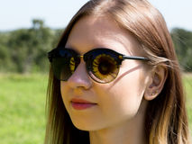 Young woman in sunglasses on the nature, sunflower reflected in glasses royalty free stock images
