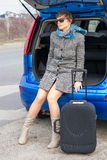 Young woman in sunglasses near the car with a suitcase Royalty Free Stock Photo