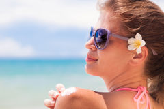 Young woman in sunglasses putting sun cream on Stock Image