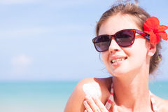 Young woman in sunglasses putting sun cream on Royalty Free Stock Images