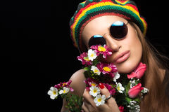 Young woman in sunglasses and rasta hat holding flowers Royalty Free Stock Images