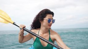 Young woman in sunglasses rowing in a boat stock video footage