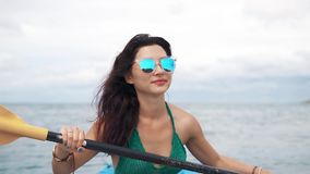 Young woman in sunglasses rowing in a kayak stock video