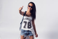 Young woman in sunglasses showing thumb up looking. At camera. Portrait of trendy girl having fun style casual concept lifestyle urban fashion royalty free stock image