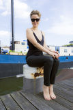 Young woman in sunglasses sitting. Against blue barge background Stock Photos