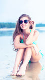 Young woman in sunglasses sitting on beach retro Royalty Free Stock Photos