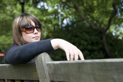 Young woman in sunglasses  sitting on bench in par Stock Photo