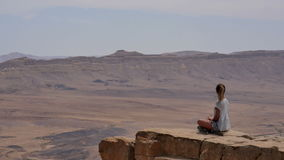 Young woman in sunglasses sitting on cliff`s edge and looking around the desert stock footage